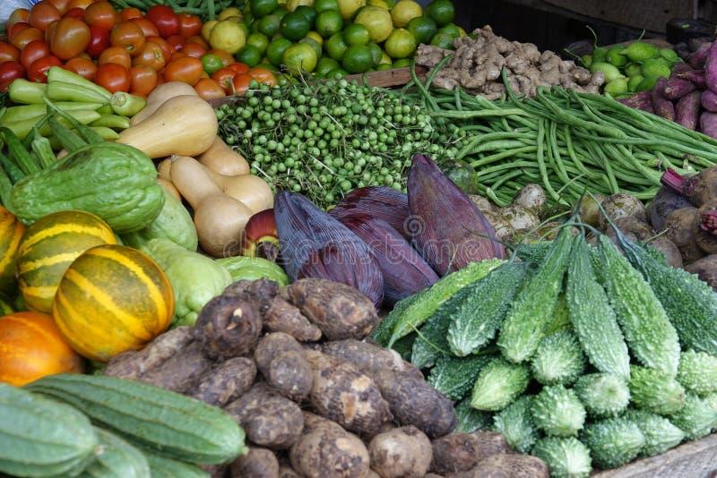 在柜台堆积的成熟菜在水果和蔬菜一个地方市场上  图库摄影