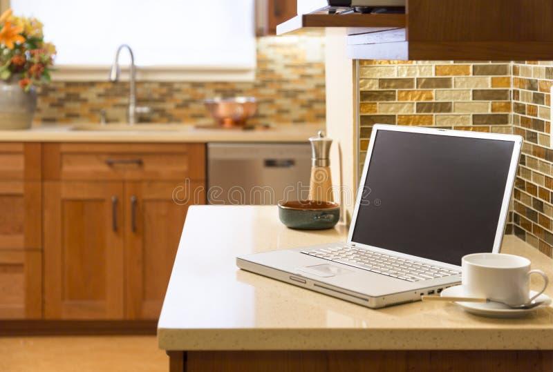 在柜台的便携式计算机在当代高级家庭厨房里 免版税库存照片