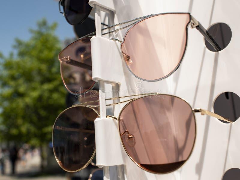在柜台的太阳镜 两个对在不同颜色的太阳镜 免版税库存图片