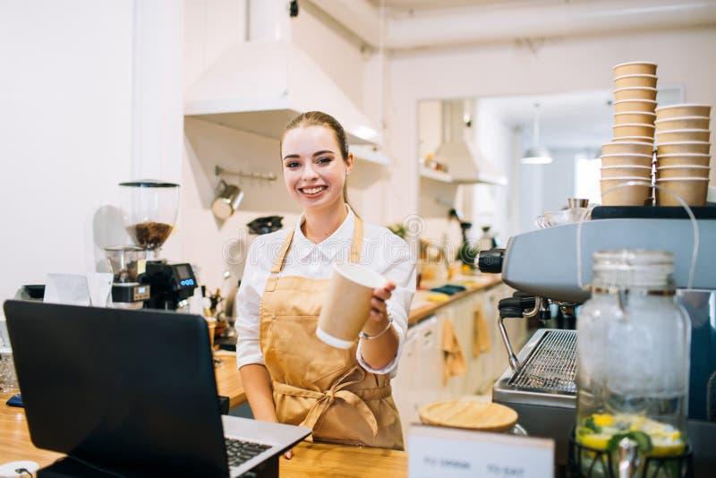 在柜台的白种人微笑的妇女barista,建议咖啡杯 库存图片