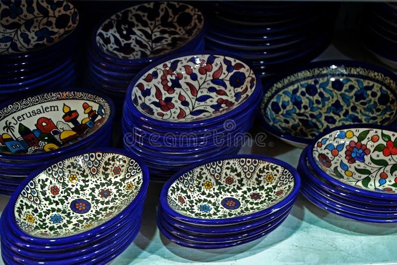 在柜台的被绘的纪念品板材在耶路撒冷,以色列商店  在一块板材的全国装饰品有蓝色边缘的 免版税图库摄影