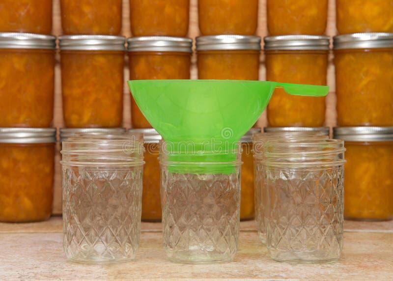 在柜台的装于罐中的桃子果酱供应与完成的瓶子在背景中 库存图片