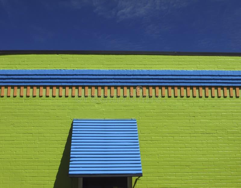 在柠檬绿大厦的蓝色窗口遮篷 库存照片