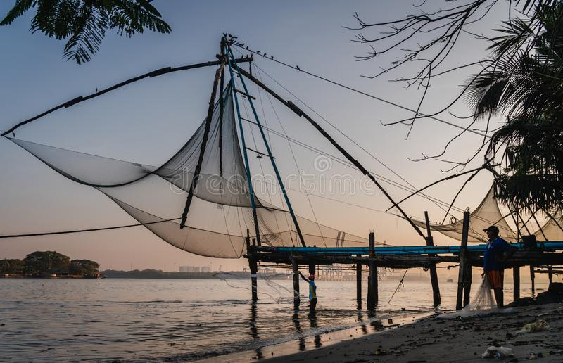 在柯枝堡,中国鱼网,喀拉拉,印度的金黄小时日出渔夫工作 免版税库存图片