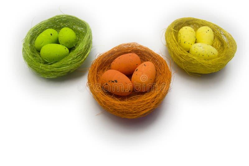 在柳条巢的多彩多姿的复活节彩蛋在白色背景 图库摄影