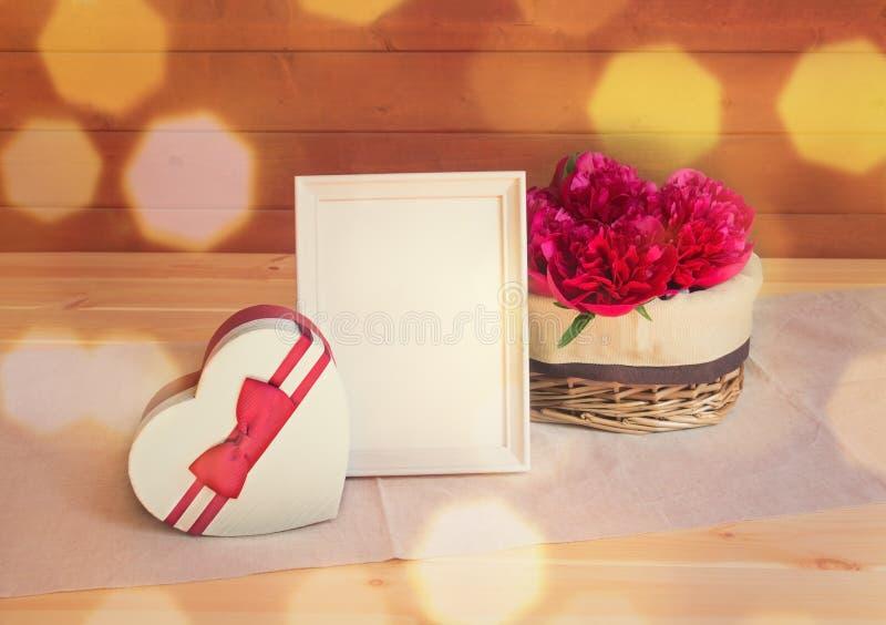 在柳条筐、心形礼物盒和白色框架的红色牡丹花在木桌上 免版税库存图片