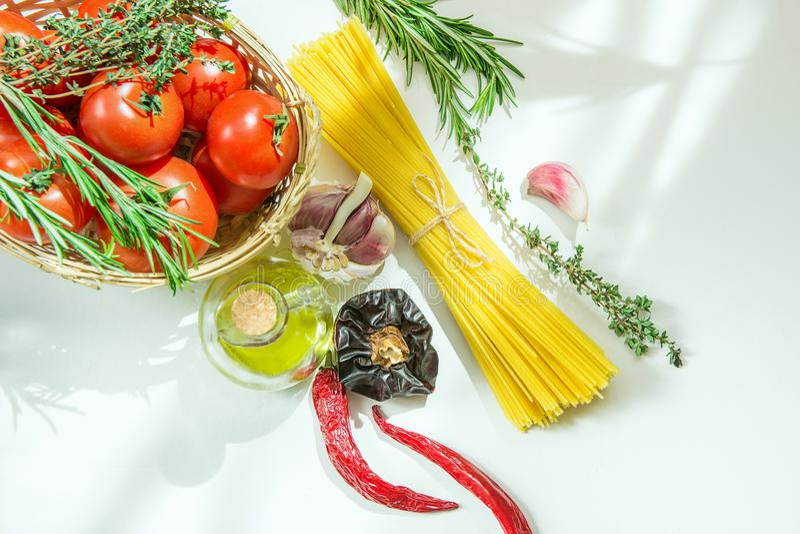 在柳条筐的成熟有机蕃茄草本罗斯玛丽麝香草 在瓶辣椒大蒜的意粉橄榄油在白色石表上 免版税图库摄影