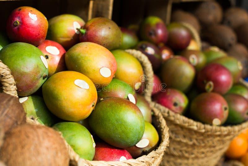 在柳条筐的成熟水多的芒果在市场柜台 免版税库存图片