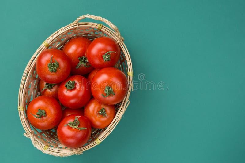 在柳条筐的新鲜的成熟有机红色蕃茄在绿松石绿色固体背景 意大利西班牙希腊地中海烹调 免版税图库摄影