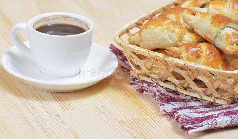 在柳条筐的热的自创新月形面包在一张木桌上 免版税库存图片