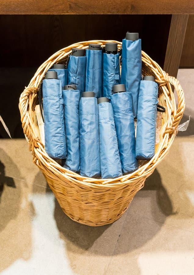 在柳条筐的蓝色可折叠的伞在水泥地板上 库存图片