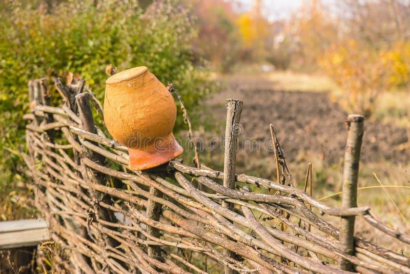 在柳条篱芭的罐 图库摄影
