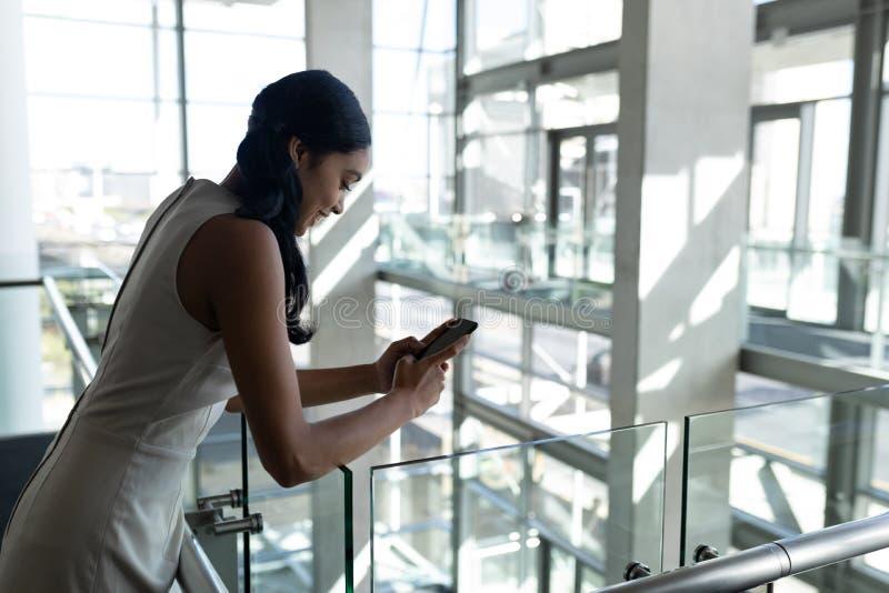 在栏杆和使用手机倾斜的女实业家背面图在办公室 免版税库存图片