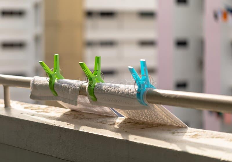 在栏杆的塑料衣裳夹子 有洗涤布料的洗衣店勾子 公寓在背景中 免版税库存照片