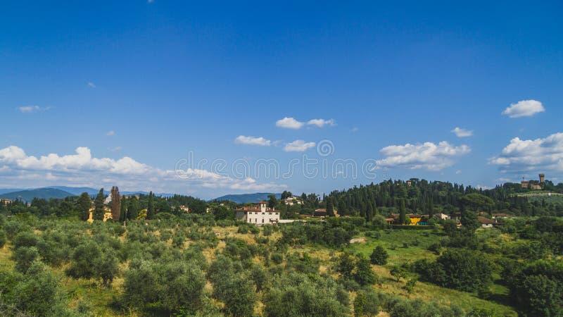 在树之间的议院在小山在佛罗伦萨外面,意大利的市中心 库存照片