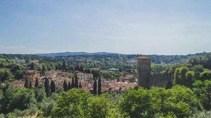 在树之间的议院在小山在佛罗伦萨外面,意大利的市中心 库存图片