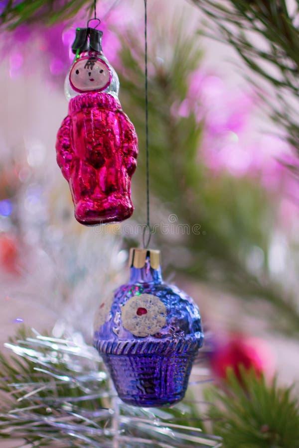 在树五颜六色篮子的特写镜头的两个圣诞节玩具 免版税库存照片