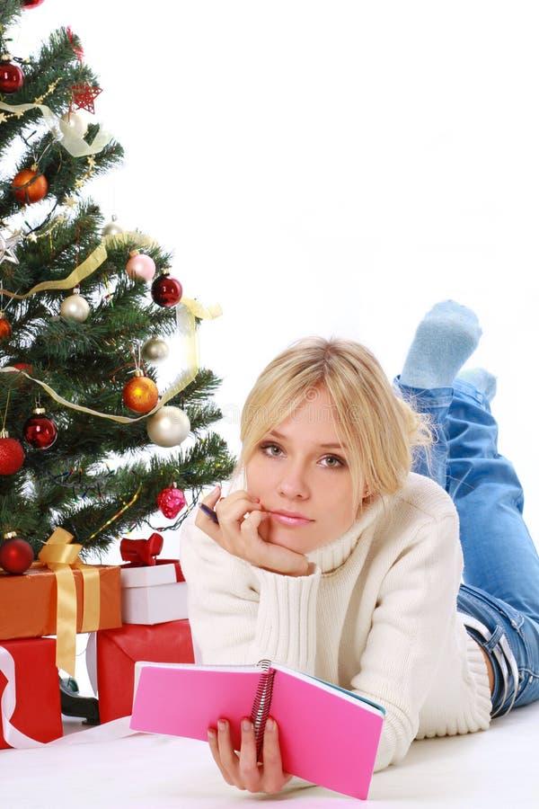 在树前面的美好的少妇说谎的圣诞节礼物在客厅 免版税图库摄影