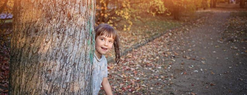 在树后的女孩皮 库存图片