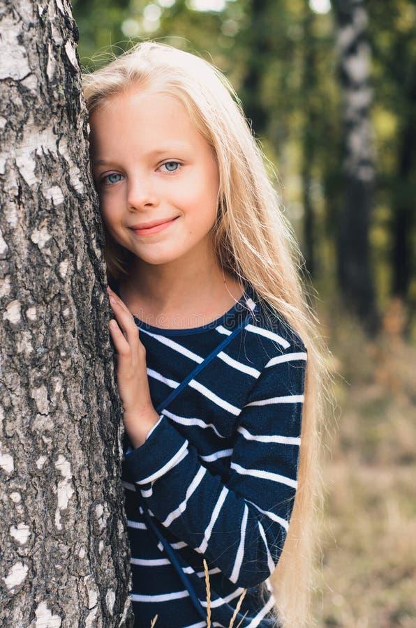 在树桦树附近的逗人喜爱的小女孩画象 库存图片