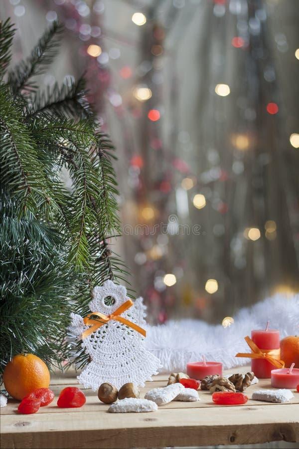 在树的圣诞节天使和在五颜六色的背景bokeh的红色蜡烛在圣诞节和新年装饰中 免版税库存照片
