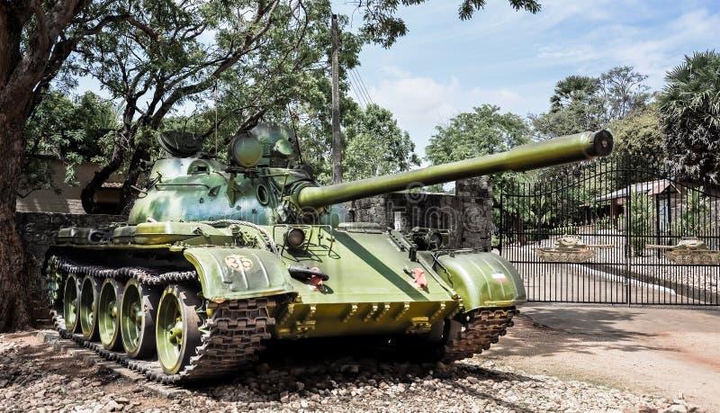 在树荫下停放的被放弃的老坦克 免版税库存图片
