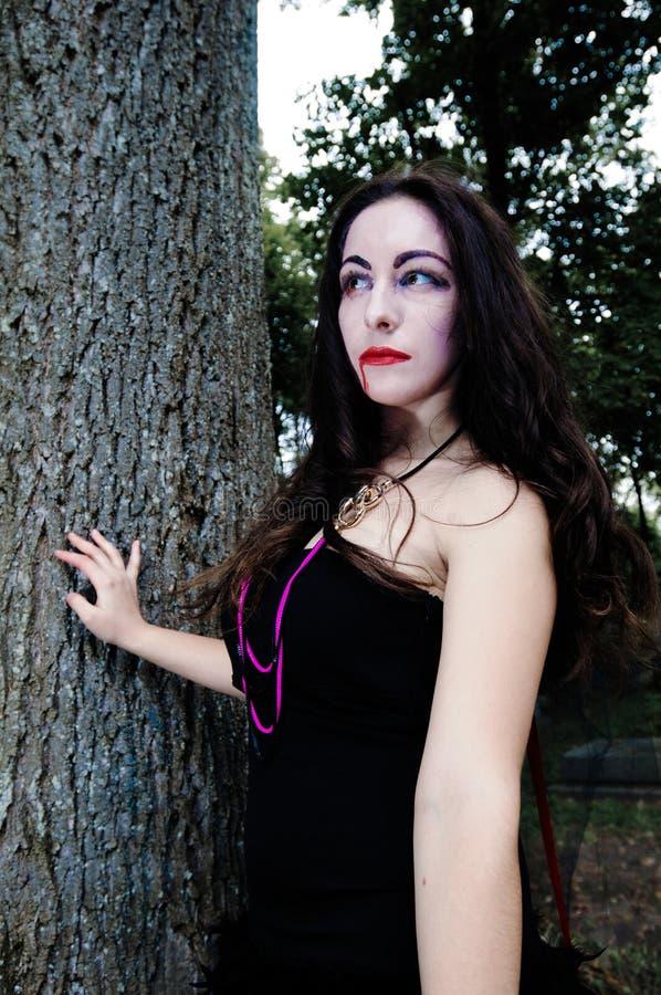 在树附近的俏丽的吸血鬼 免版税库存图片