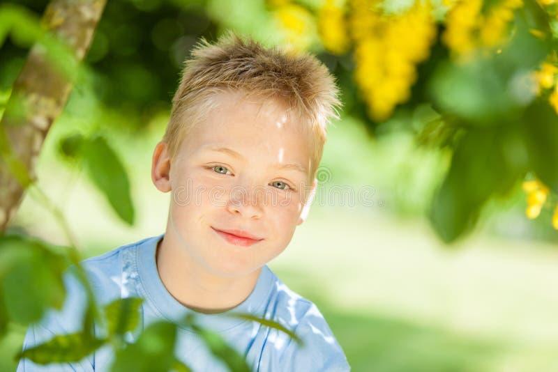 在树附近的逗人喜爱的白肤金发的男孩 免版税图库摄影
