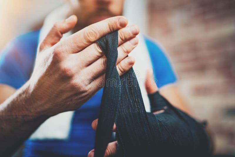 在栓黑拳击绷带的年轻运动员的男性手上的特写镜头视图 放松在艰苦kickboxing以后的拳击手人 免版税图库摄影