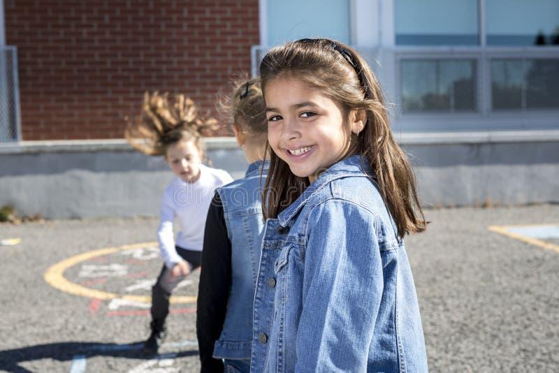 在校园的跳房子与朋友一起使用 库存图片