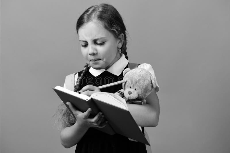 在校服的学生有辫子的 女孩拿着玩具熊 免版税图库摄影