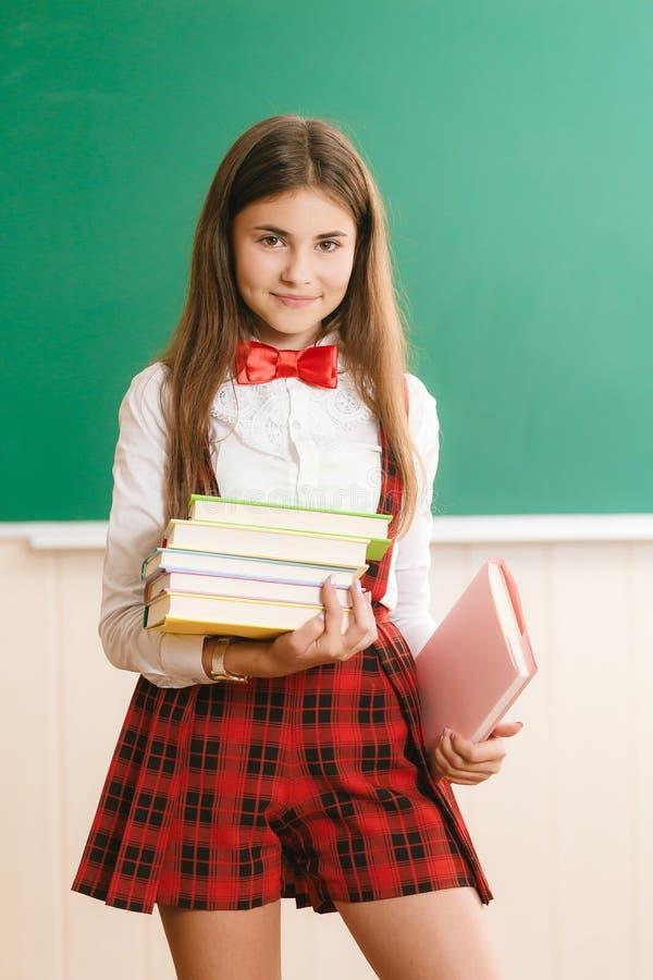 在校服身分的学生在黑板和举行课本对面的学校课程 免版税库存图片