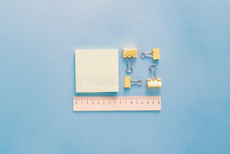 在样式安置的学校用品在蓝色背景 回到学校和教育概念 作为统治者,纸夹的办公用品 库存图片