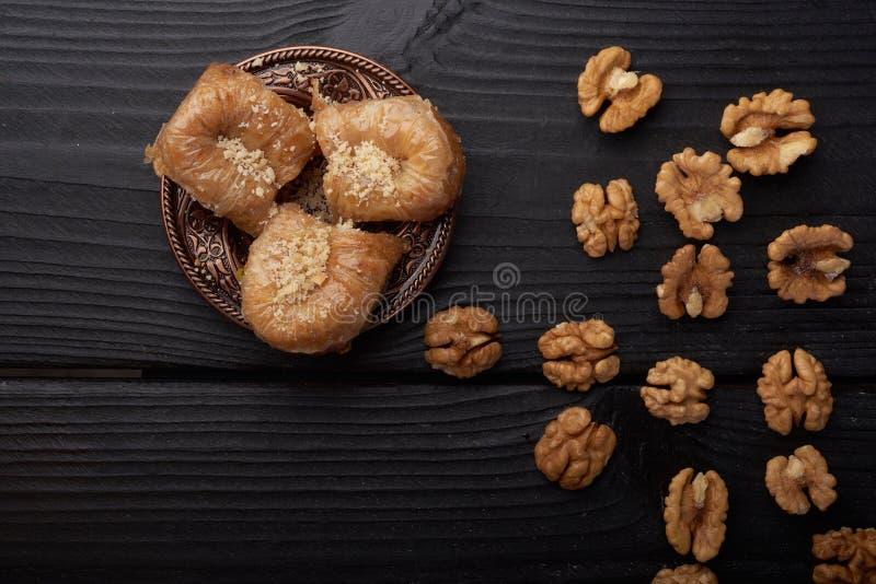 在核桃附近的土耳其果仁蜜酥饼在黑木背景 库存图片
