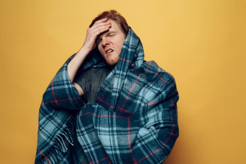 在格子花呢披肩包裹的年轻人咳嗽与头疼 免版税图库摄影