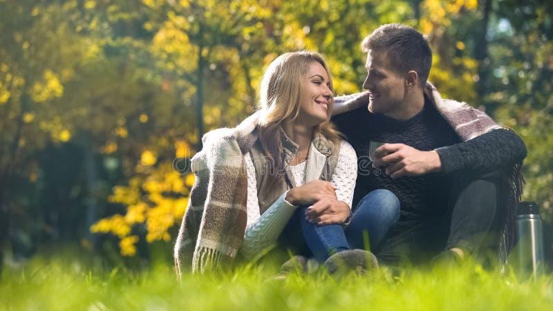 在格子花呢披肩和妇女盖的男人坐在秋天公园,谈的和饮用的茶 库存图片