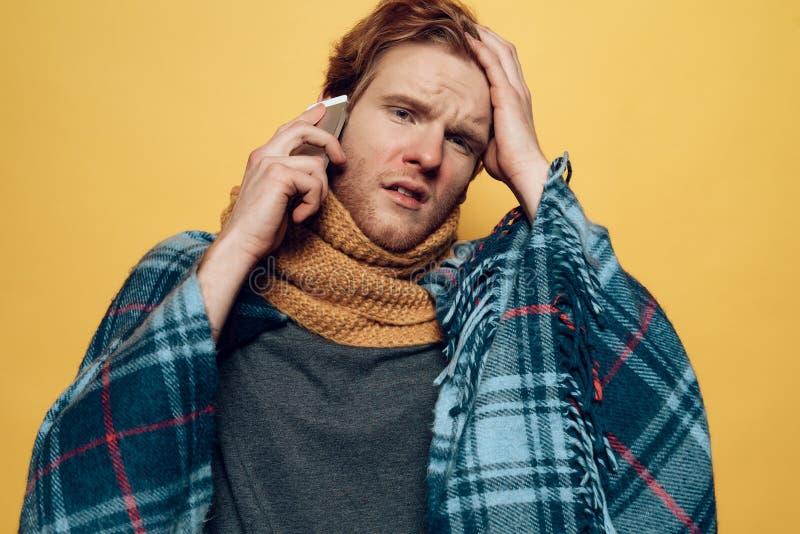 在格子花呢披肩谈的电话包裹的年轻病的人 库存图片