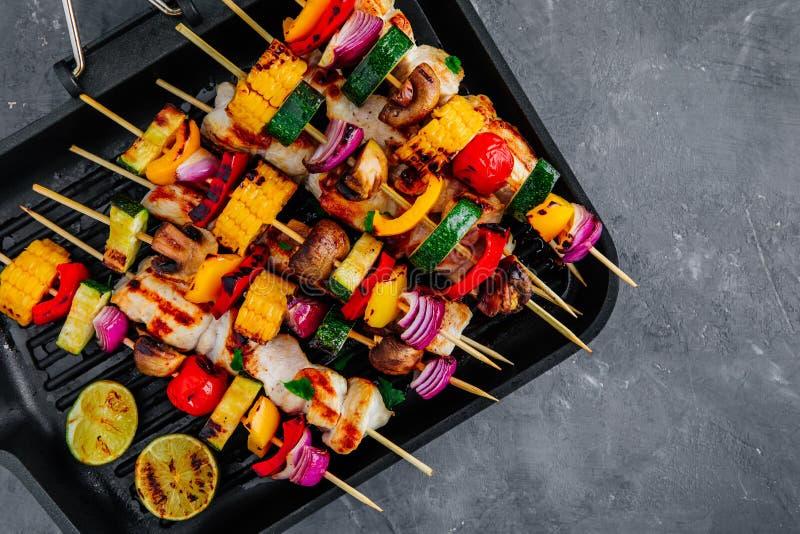 在格栅平底锅,顶视图的烤菜和鸡串 免版税库存照片