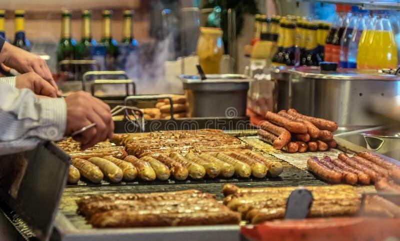 在格栅栅格的多味腊肠在一个摊在圣诞节市场上我 免版税库存图片