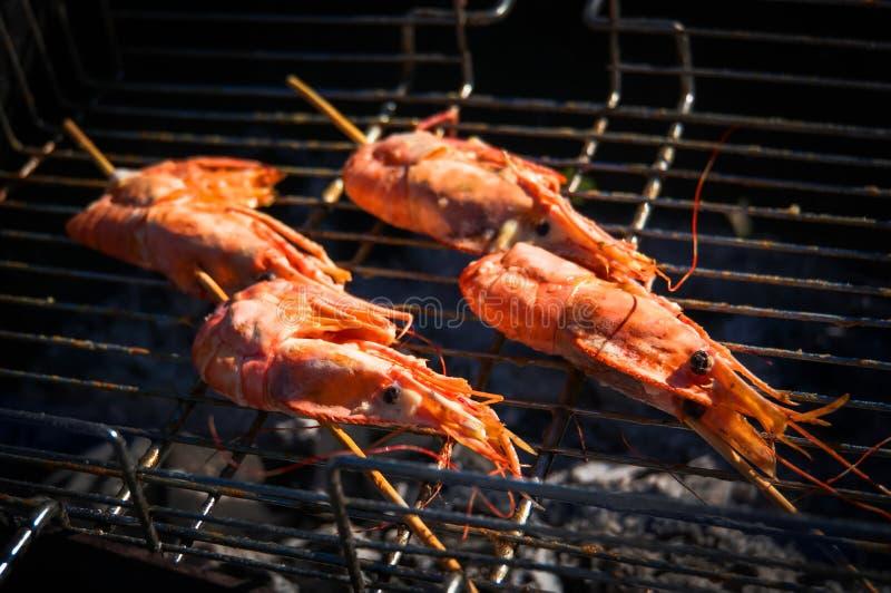 在格栅的可口大虾唾液与火焰在背景中 库存图片