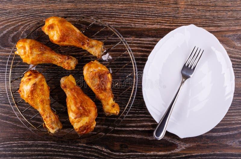 在格栅的炸鸡腿在板材,在盘的叉子在桌上 顶视图 免版税库存图片