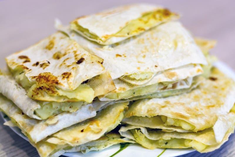 在格栅的麦子玉米粉薄烙饼,用土豆和葱,快餐,野餐的鲜美平的面包 库存照片