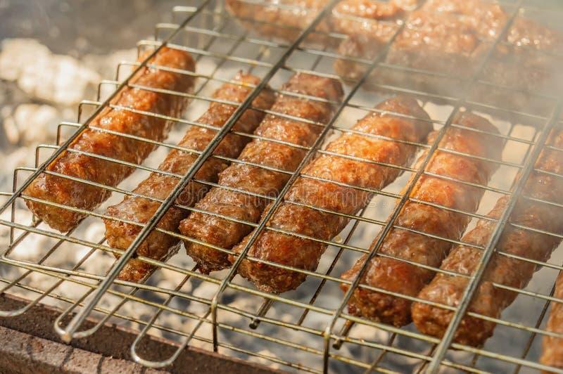 在格栅的Cevapcici在被烤开火 夏天烤肉周末 Shashlik是一个全国白种人盘 免版税库存图片