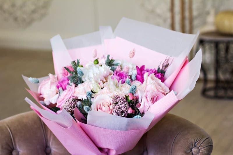 在桃红色包装纸的美丽的花束 玫瑰和其他精美美丽的花 库存图片