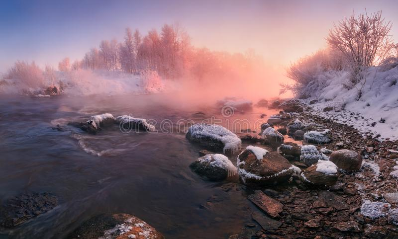 在桃红色口气的冬天风景:冷淡的早晨,河在Frazil弄脏了水、在雾的石头和太阳 与斯诺伊T的白俄罗斯风景 免版税库存图片