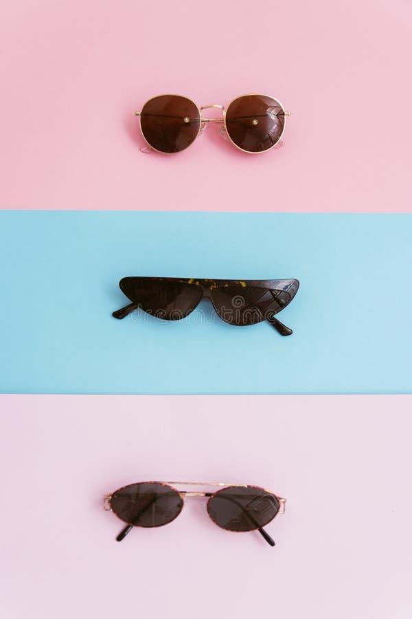 在桃红色和蓝色淡色背景的三副太阳镜 夏天和时髦的假期的概念 库存照片
