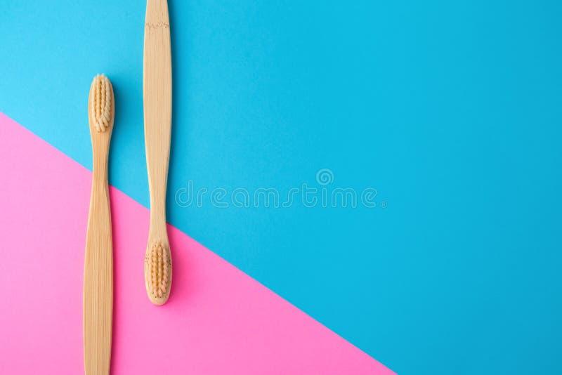 在桃红色和蓝色背景的竹牙刷 库存图片