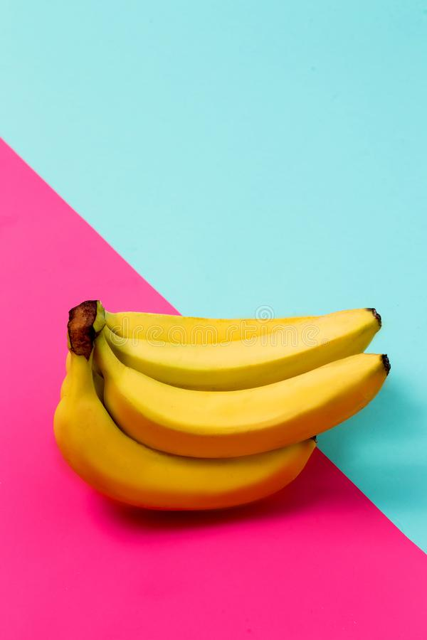 在桃红色和蓝色背景的香蕉群 免版税库存照片
