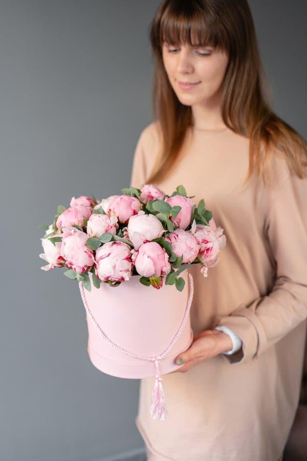 在桃红色圆的箱子的桃红色牡丹 美丽的牡丹花在编目或网络商店的妇女手上 花卉商店概念 免版税库存照片