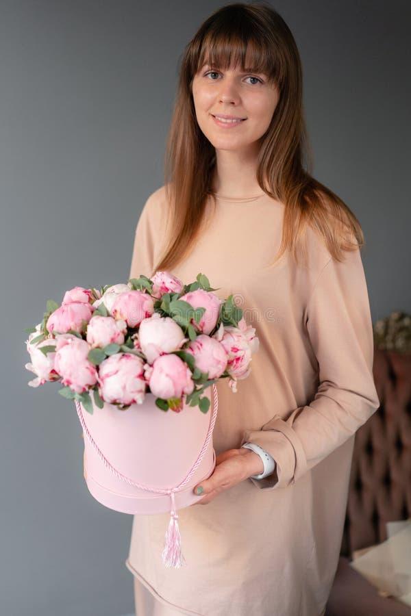 在桃红色圆的箱子的桃红色牡丹 美丽的牡丹花在编目或网络商店的妇女手上 花卉商店概念 库存照片